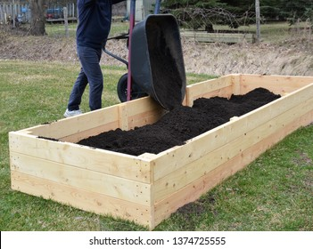 Filling up a newly constructed garden box with fresh soil.