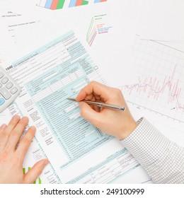 Filling out 1040 US Tax Form - studio shot