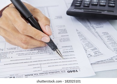 Filling out income tax forms with calculator and pen