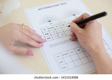Filling papers. Accurate ophthalmologist with neat manicure holding black pen and writing indicators of astigmatism test