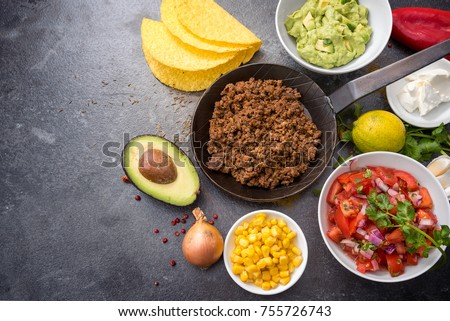 filling tacos with roasted beef, tomatoes, corn and guacamole, all ingredients on a dark stone background with copy space, top view from above, selected focus, narrow depth of field