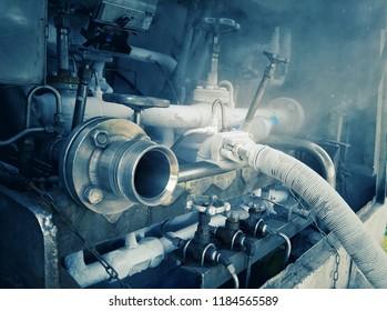 Filling tanker truck with liquid nitrogen. Cold metal pipe smoking from transferring liquid nitrogen