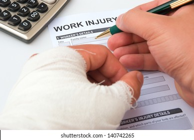 filling up a work injury claim form with a wrapped hand, calculator in corner, medical and insurance concept