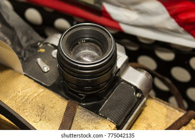 Film camera of the old model with a black metal case and a leather strap
