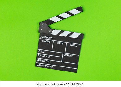 Film clapper board on green background top view