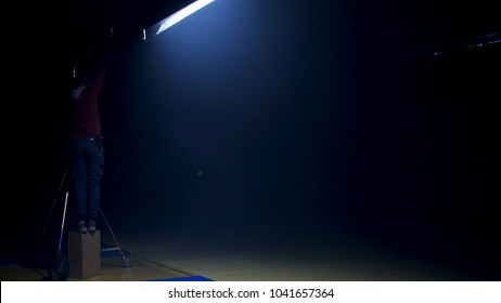 The film crew works on creation of a videoclip. Gaffer prepares diffusion for a light in the studio. Gaffer puts blue gel on a fresnel light on video production set