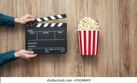 Film director holding a clapper board and popcorn, filmmaking and cinema concept
