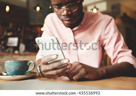 Film effect. Handsome African student in shirt and glasses using mobile phone, looking at the screen with serious and concentrated expression while having coffee at a cafe after classes at university