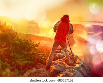 Film grain effect. Happy photo enthusiast  enjoy  photography of  fall daybreak in nature on cliff on rock. Dreamy fogy landscape