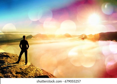 Film grain effect. Man stands on rock above valley within daybreak and watch to hot Sun. Beautiful moment the miracle of nature