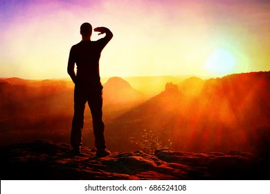 Film grain effect.  Young sportsman shadowing his eyes from the bright light of the daybreak Sun