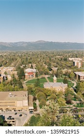 A film image and aerial view of the University of Montana Campus with the oval and main hall in the center taken from Mount Sentinel trail in Missoula, Montana with mountains in the distance.