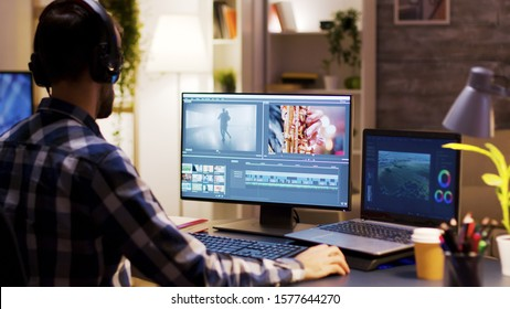 Film maker pointing at the monitor in home office while working on post production for a movie. Video editor wearing headphones.
