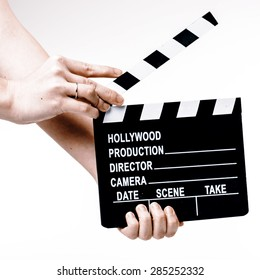 Film or Movie flapper in woman�´s hands on white background