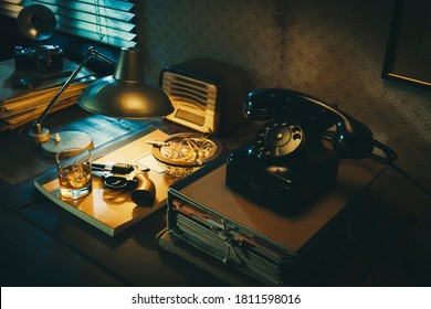Film noir detective desktop with revolver, whiskey and ashtray, thriller and suspense concept