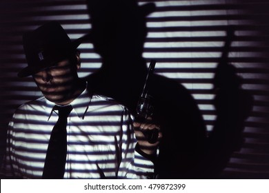 Film Noir Man With Gun Blinds Shadow. Man in white shirt, black tie and hat standing holding gun in shadows of blinds, in film noir style.