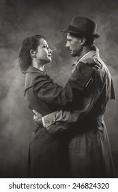 Film noir: romantic loving couple embracing in the dark, 1950s style