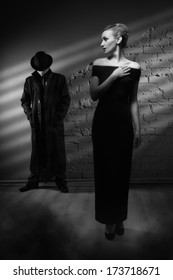 Film noir. Woman in a long black dress and a man in a raincoat and hat