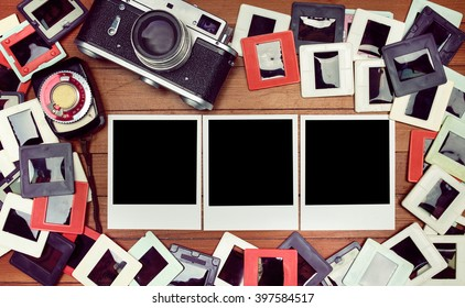 Film photos on the table. retro camera and some old photos on wooden table. Vintage look