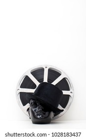 film reel of old movies and black dummy head with hat on white background.concept cinema