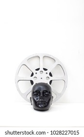 film reel of old movies and black dummy head on white background.concept cinema