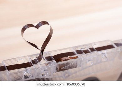 Film in a shape of heart from Compact Cassette. Love for music and songs. Wooden background