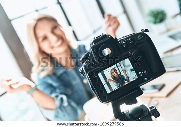 Filmen. Schöne junge Frau in zwangloser Kleidung lächelnd beim Aufnehmen des Videos