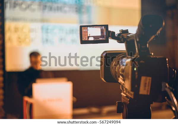 Filming creative video footage with professional video camera during the lection or meeting