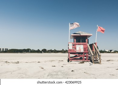 (Film&Instagram Concept): Red Life Guard Stand with American Flag on the White-Sand Beach in Florida (Siesta Key beach), Sarasota, Florida.  Florida is well known for beaches, sands, and sun