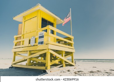(Film&Instagram Concept): Yellow Life Guard Stand with American Flag on the White-Sand Beach in Florida (Siesta Key beach), Sarasota, Florida.  Florida is well known for beaches, sands, and sun