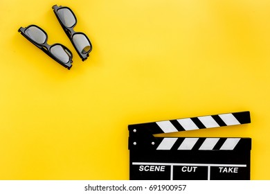Filmmaker accessories. Clapperboard and glasses on yellow background top view copyspace