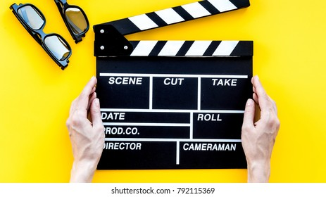 Filmmaker accessories. Clapperboard and glasses on yellow backgr