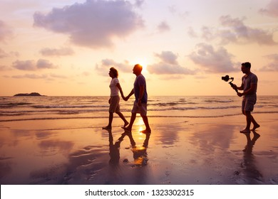 filmmaker filming video of couple with camera stabilizer on the beach at sunset, professional videographer working on film