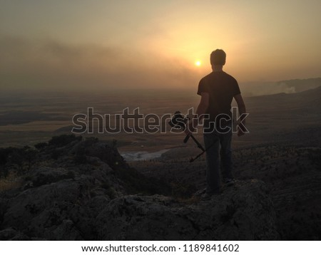 Filmmaker overlooking valley in norther Iraq at sunset