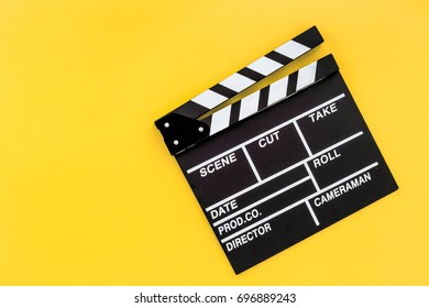 Filmmaker profession. Clapperboard on yellow background top view copyspace