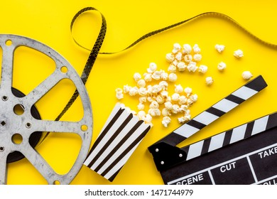 Filmmaker profession with clapperboard, popcorn and video tape on yellow background top view