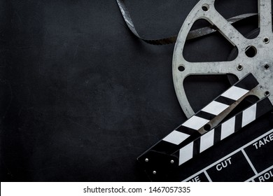 Filmmaker profession with clapperboard and video tape on black background top view copyspace