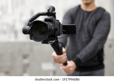 filmmaking, videography, hobby and creativity concept - close up of modern dslr camera on 3-axis gimbal in male hands