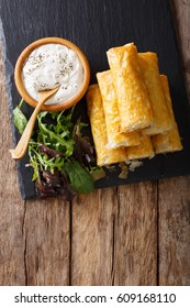Filo rolls with meat, eggs and greens close-up and yogurt on the table. Vertical view from above