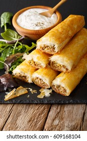 Filo rolls stuffed with minced meat and eggs close-up and yogurt on the table. vertical
