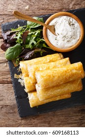 Filo rolls stuffed with minced meat and eggs close-up and yogurt on the table. Vertical view from above