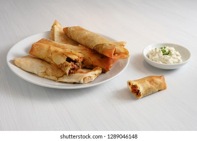 filo or yufka dough rolls stuffed with a spicy meat filling and cheese curd on a white painted table, copy space, selected focus, narrow depth of field
