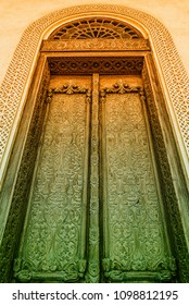 A filtered dual color image of an elaborately carved exterior door with a glass arch and a carved gypsum surround in a restored traditional arabian house.