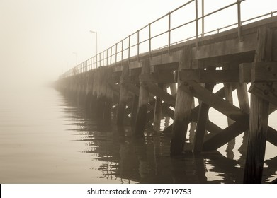 Filtered image of fog over ocean, lake or river water with wooden jetty, blurred background, copy space.