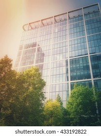 Filtered image of modern glass building exterior and trees around it