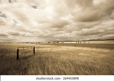 Filtered image of remote rural farming country in dry arid outback Australia, with storm clouds, wide open space of fields and meadows, copy space, blurred background.