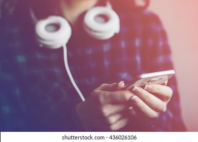 Filtered image of young lady holding a smart phone and listens to music from her headphones