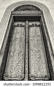 A filtered monochrome image of an elaborately carved exterior door with a glass arch and a carved gypsum surround in a restored traditional arabian house.