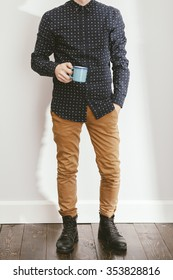 filtered photo of a young stylish man holding a coffee