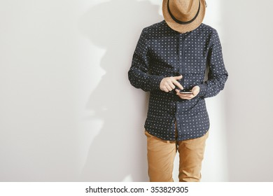 filtered photo of a young stylish man holding a smartphone